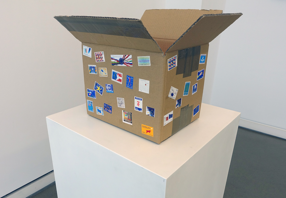 Bill Balaskas, Pandora, 2016, mixed media: carton box, inflatable armband, styrofoam packing peanuts, commemorative EU postage stamps, 33 x 50 x 40 cm