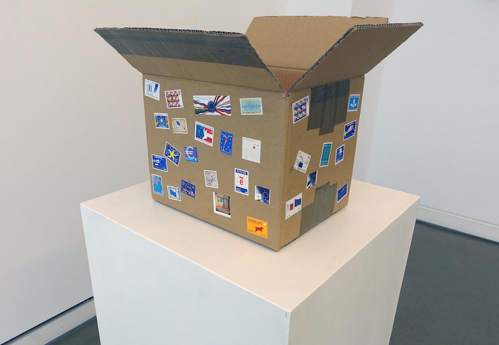 Bill Balaskas, Pandora, 2016, mixed media: carton box, inflatable armband, styrofoam packing peanuts, commemorative EU postage stamps, 33 x 50 x 40 cm